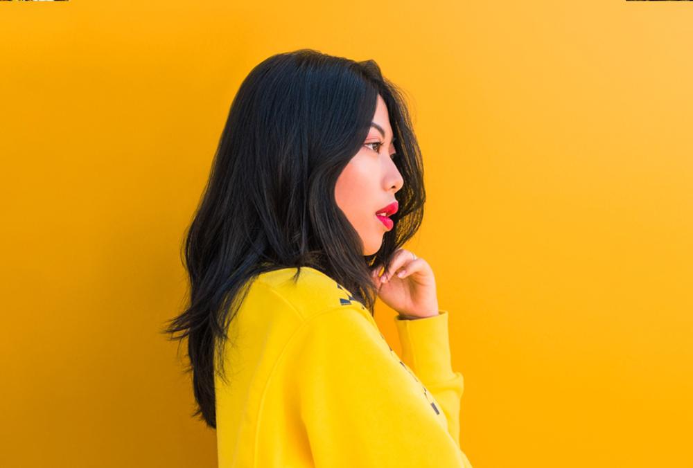 colorblocking portret van model Sindy met gele trui en rode lippenstift tegen een gele achtergrond